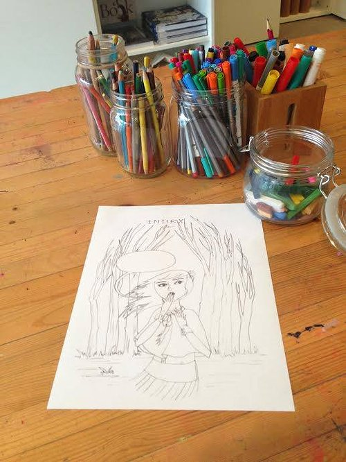 drawing of a woman on a wooden table with many pencils and pens sitting in jars in the background