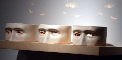 three sculptures of the centre portion of a head on a shelf, eyes are made of glass