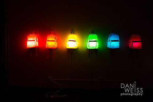photo artwork of backpacks with lights inside on a gallery wall