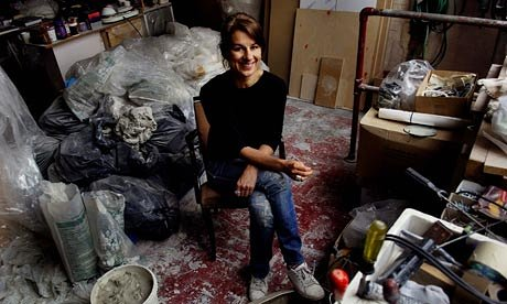 woman sitting on a chair in her art studio. she is surrounded by clay and pottery supplies