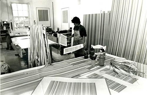 bridget riley wearing an apron in her art studio. There are very large artworks in the foreground on a table. Black and white image.