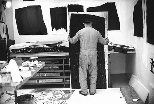 photograph of Richard Serra facing away from the camera while holding his artwork in his art studio
