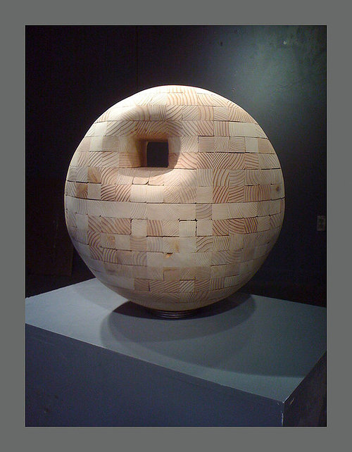 wood sculpture of a sphere with a whole near the top