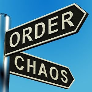 street sign pointing to two directions that says order on one and chaos on the other