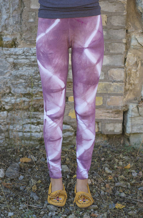 A photo of a model wearing hand-dyed purple and white leggings