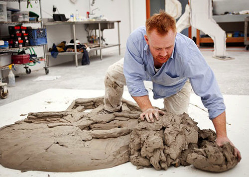 A picture of Thomas Houseago sculpting a large lump of clay on the floor of his studio