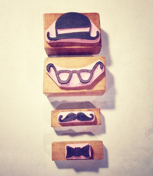 A series of rubber stamps with a hat, mustache, glasses, and bowtiees