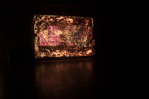 An installation view of a projector screen showing film negatives that have been painted and scratched
