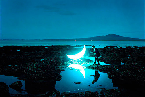 A man and the moon on a shore