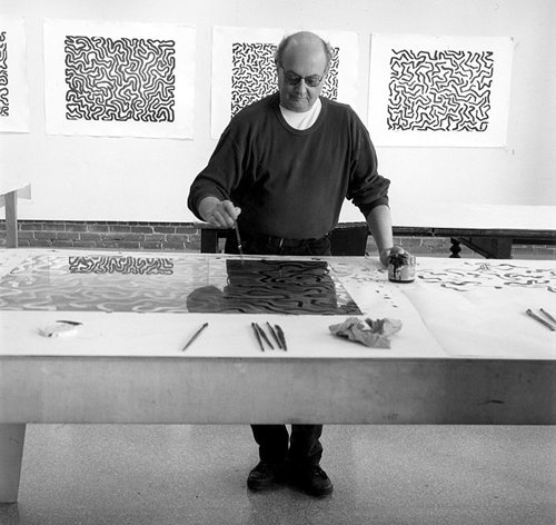 A black and white photograph of Sol Lewitt working in the studio