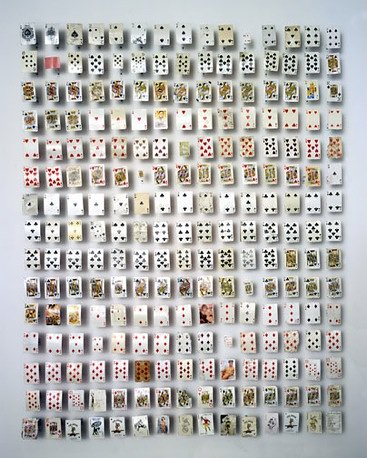 A series of playing cards mounted in a grid on the wall