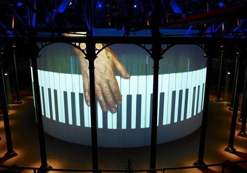 A photo of a projection installation featuring a close-up hand playing a piano