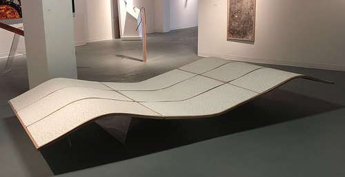 An installation view of a sculpture made of ceiling panels