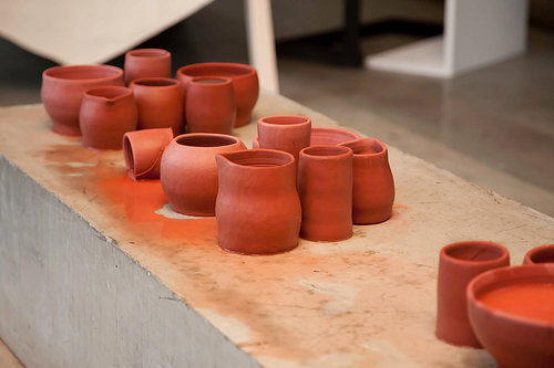 An installation view of a ceramic sculpture made of unfired clay vessels
