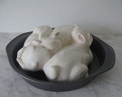 A plaster sculpture of sleeping rabbits in a pie tin
