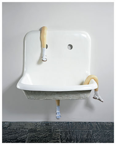 A sculpture of a household sink with strange, disproportionate legs where the pipes should be
