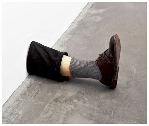 A realistic sculpture of a man's lower leg sticking out of a wall