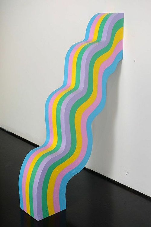 A sculpture of a wavy rainbow coming out of the wall