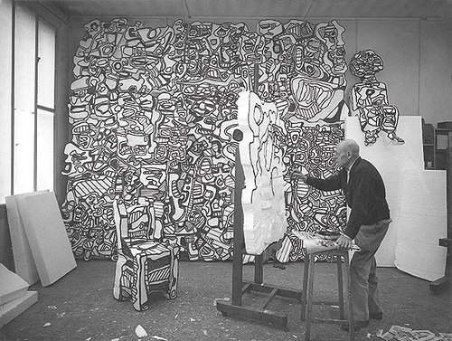 A black and white photo of Jean Dubuffet working in his art studio