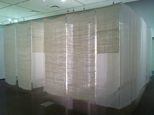 An installation view of an indoor labyrinth with walls of thin white fabric