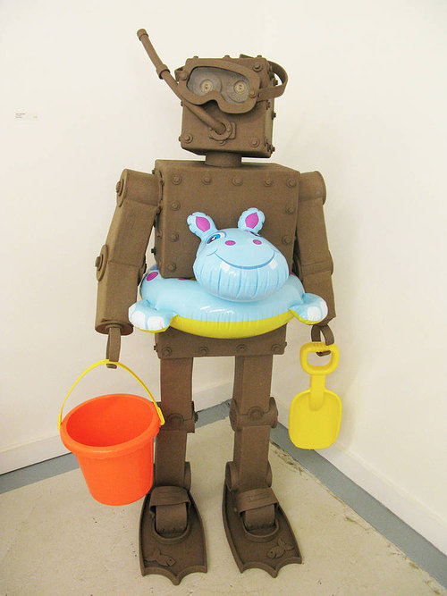 A standing clay sculpture of a robot dressed for the beach