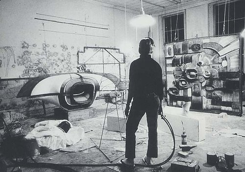 A blback and white photo of Eva Hesse in her studio looking at an in-progress work
