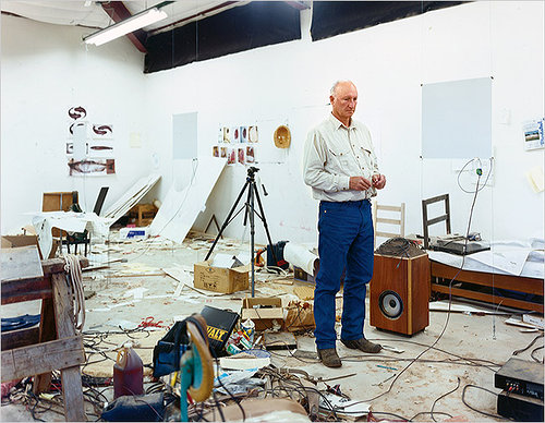 Bruce Nauman standing in his very messy studio space