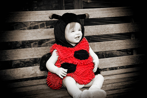A partially coloured photo of a young girl wearing a ladybug costume