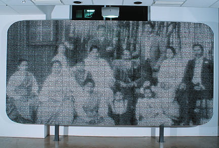 A billboard covered in printed pieces of one larger image, a family portrait