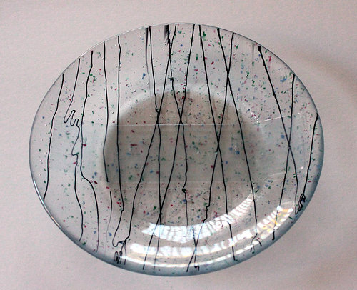 A handmade glass dish with clear glass and confetti embedded