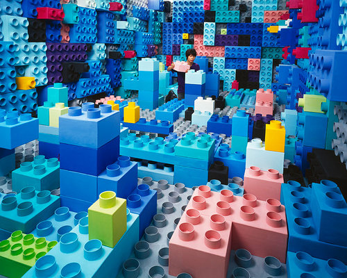 A photograph of a woman playing in a room filled with giant legos