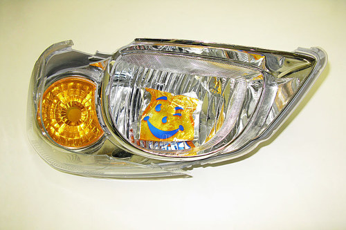 A photograph of a piece of a car's headlight, with a logo sticker on it