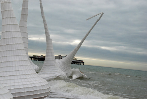 A photo of several large, lantern-like constructions being swallowed by the tide