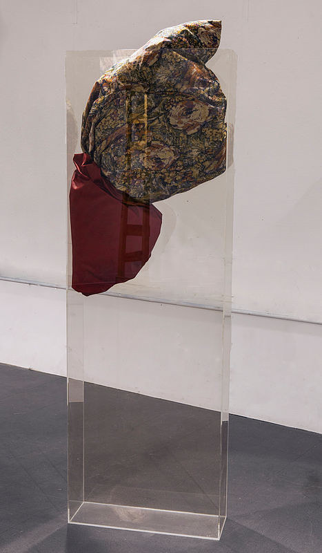 An installation with some pieces of fabric trapped in a plexiglass box