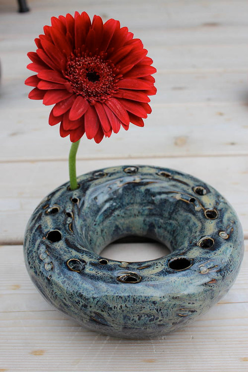A hollow ceramic ring with holes where flowers can be placed