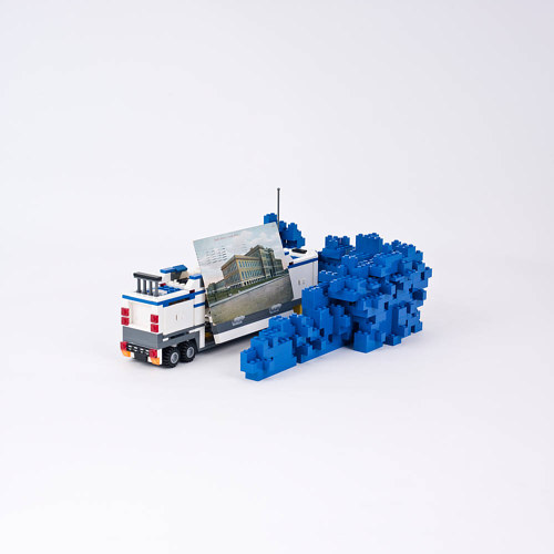 A small sculpture created from blue Lego blocks and a photograph of a building