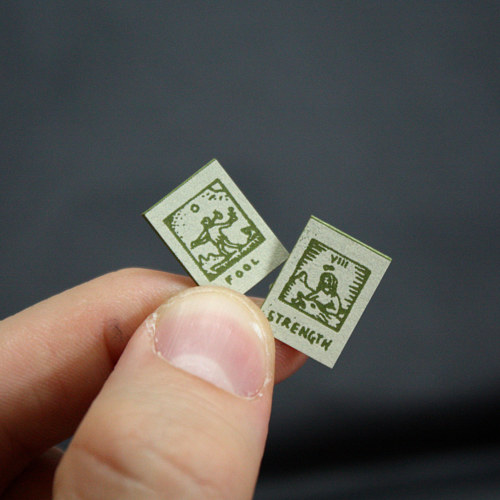 A photo of two tiny tarot cards being held in someone's finger's