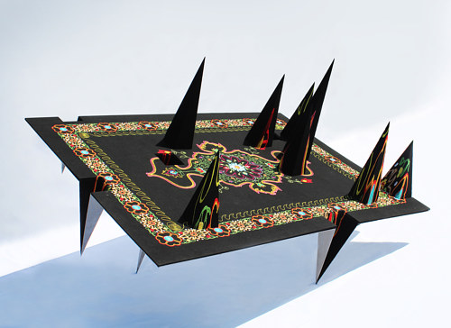 A steel sculpture that looks like a traditional carpet with spikes pointing out of it