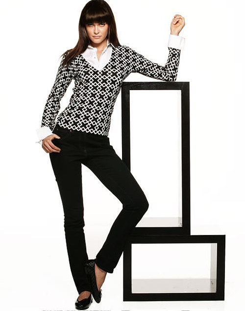 A photo of a model wearing a patterned sweater and black pants