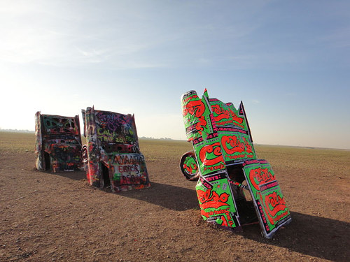 An installation of graphic-wrapped cars half buried in the desert