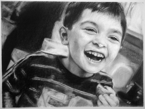 A charcoal portrait of a young boy laughing