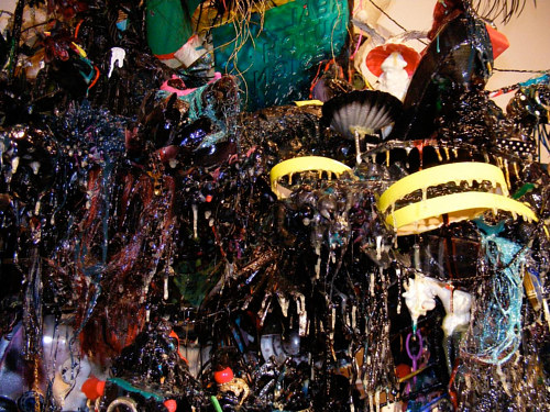 A close up installation photo of a number of dark-coloured objects hung from a wall