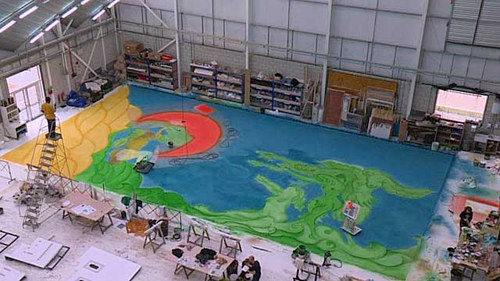 An aerial photo of Chris Ofili working on a very large painting in his studio