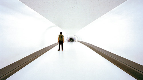 A photo of a person standing in a tunnel lit with intensely bright white light