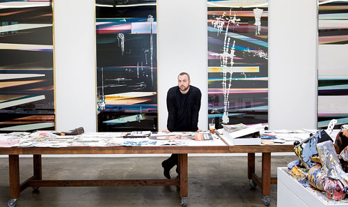 A photograph of Walead Beshty standing in front of three large works in his studio