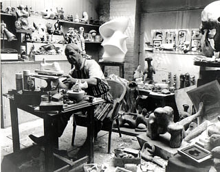 A black and white photograph of Henry Moore working in his studio