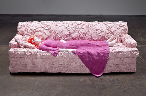 A fibreglass sculpture of a woman lying on a couch