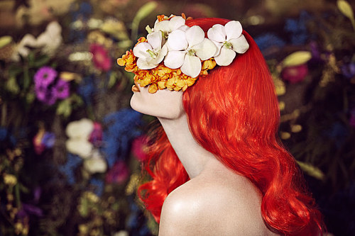 A photograph of a woman with bright orange hair wearing a mask of flowers