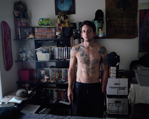 A photo of a man standing in his bedroom