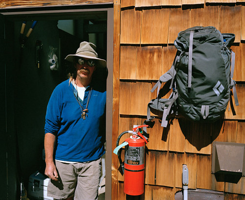 A photo of a man standing inside a cabin in Yosemite